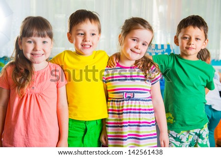 Group of four happy preschoolers standing in playroom - stock photo