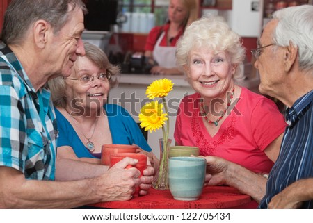 Group of four happy senior citizens at restaurant - stock photo
