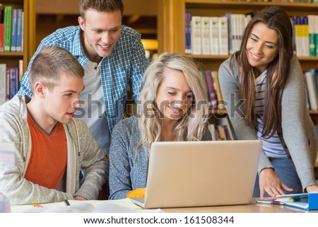 Group of four happy students using laptop at desk in the college library