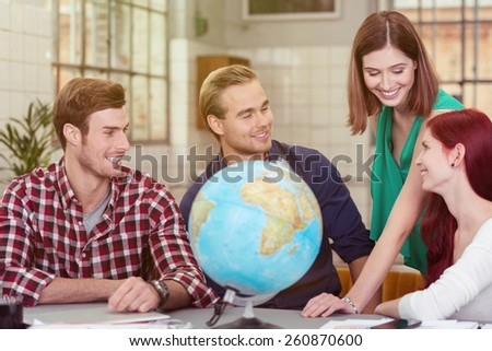 Group of Four Happy Young Friends Talking at the Worktable with Desk Globe - stock photo