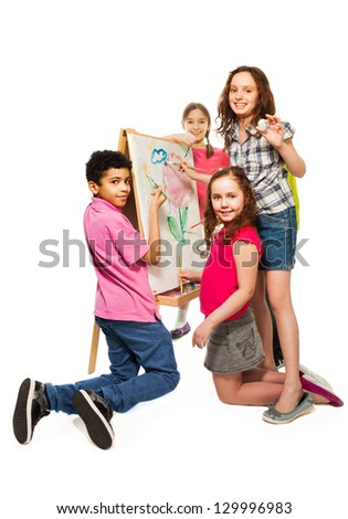 Group of four kids, boys and girls painting image together with paintbrushes on the white canvas