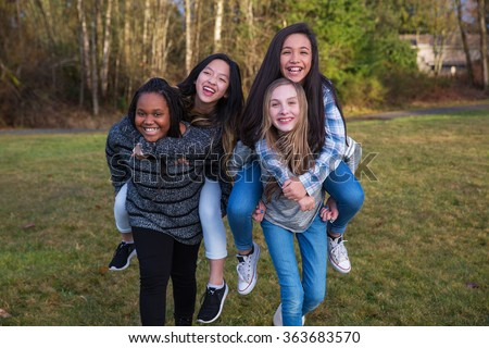 Group of four kids playing and giving piggyback rides - stock photo