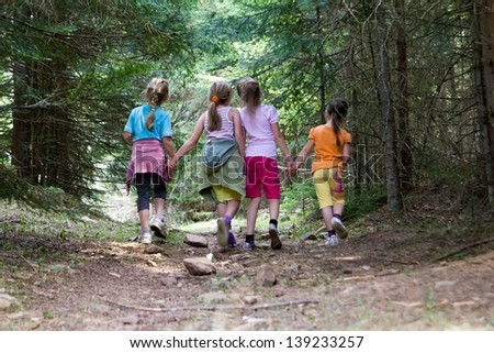 Group of four little girls running in the forest