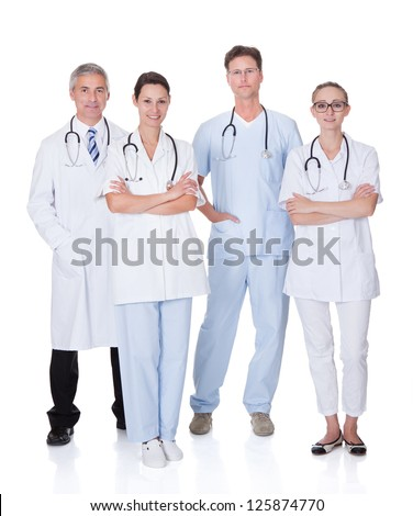 Group of four medical professionals with a male doctor and surgeon and two females doctors on a white studio background
