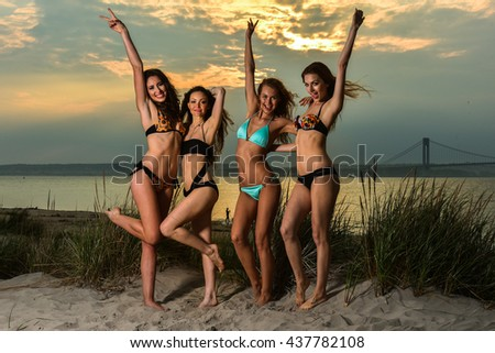 Group of four models wearing bikinis posing at sunset beachphotoshoot. - stock photo