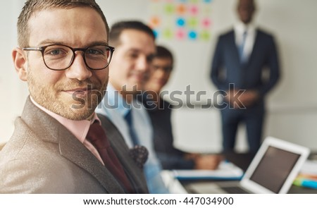 Group of four multi-cultural executives in a meeting at their office in front of laptop and white board - stock photo