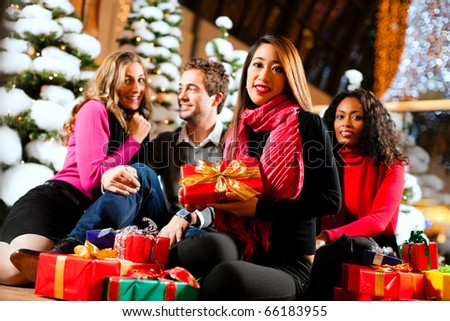 Group of four people - diversity - sitting amid artificial snow covered fir trees and lights with Christmas presents in a shopping mall