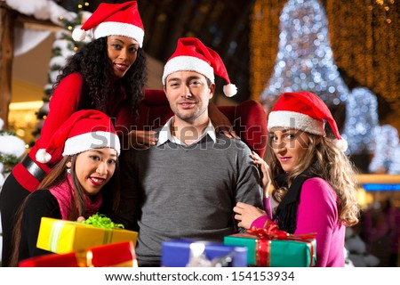 Group of four people - diversity - with Santa hats sitting amid artificial snow covered fir trees and lights with Christmas presents in a shopping mall