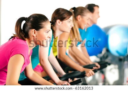 Group of four people in the gym, exercising their legs doing cardio training