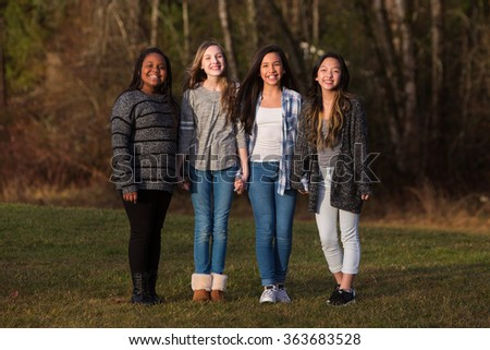 Group of four pretty young girls with cultural diversity holding - stock photo