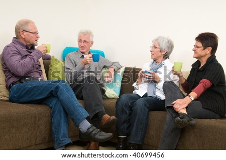 Group of four seniors drinking coffee, chatting and having a great family time together.