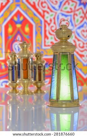Group of Four Shiny Lanterns over Ramadan Fabric - stock photo