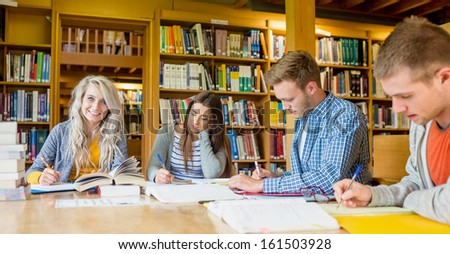 Group of four students writing notes at desk in the college library - stock photo