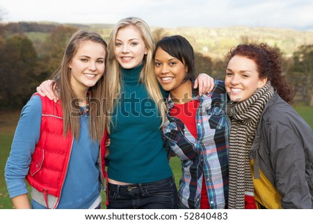 Group Of Four Teenage Female Friends In Autumn Landscape