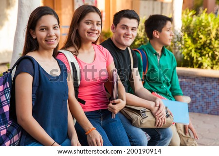 Group of four teenage friends hanging out in high school - stock photo
