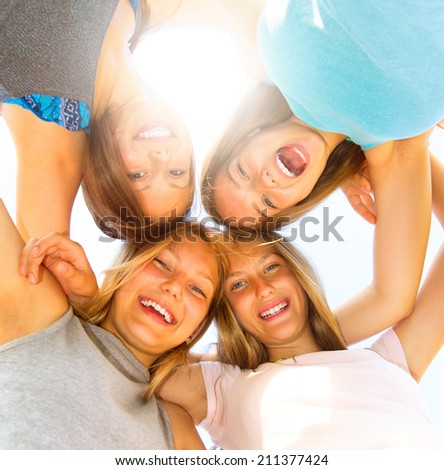 Group of Four Teenage Girls having fun outdoors. Friendship concept. Group of smiling friends staying together, looking at camera and laughing over blue sky. Joyful girlfriends making a huddle - stock photo