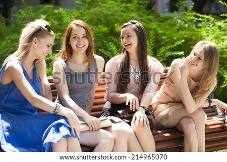 Group Of Four Teenage Girls Sitting On Bench In summer Park