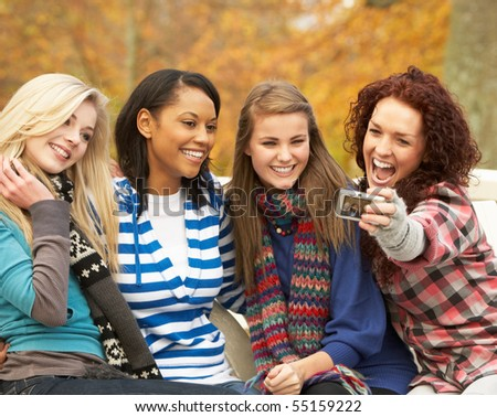 Group Of Four Teenage Girls Taking Picture With Camera Sitting On Bench In Autumn Park - stock photo