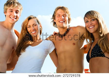 Group of four very beautiful people - men and women - on the beach  - stock photo