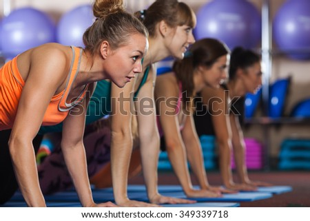 group of four woman at gym push up workout exercise