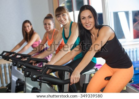 Group of four woman in the gym, exercising their legs on cycles - stock photo