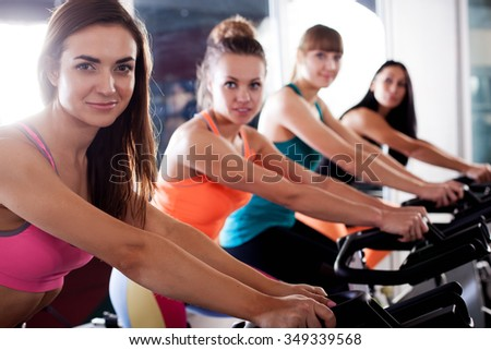 Group of four woman in the gym, exercising their legs on cycles, closup view - stock photo