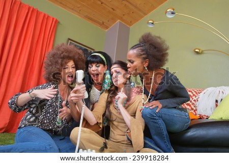 Group of four women in 1960s clothing yelling into telephone