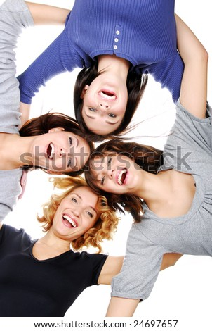 Group of four young adult girls in circle looking at camera - stock photo