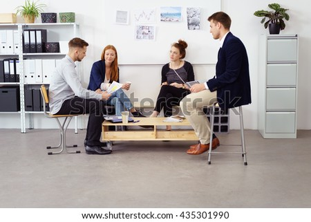 Group of four young adult male and female business persons seated around small table in bright white office with bulletin board and shelving on walls - stock photo