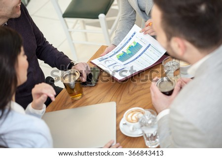 group of four young business people discussing an interesting idea in the cafe