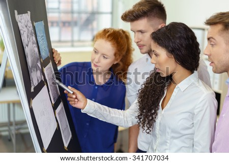 Group of Four Young Business People Discussing on Proposed Designs Pasted on a Flip Chart inside the Office. - stock photo