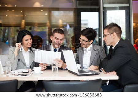 Group of four young business people gathered together at a table discussing an interesting idea in the cafe