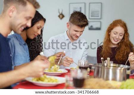 Group of Four Young Friends Having their Lunch Together at Home as they Celebrate Something. - stock photo