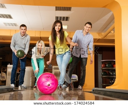 Group of four young smiling people playing bowling