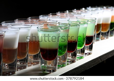 Group of fresh cold colorful yummy cocktail shooters strong drinks in beautiful drinking transparent glasses standing in row on white bar studio closeup on black background, horizontal picture - stock photo