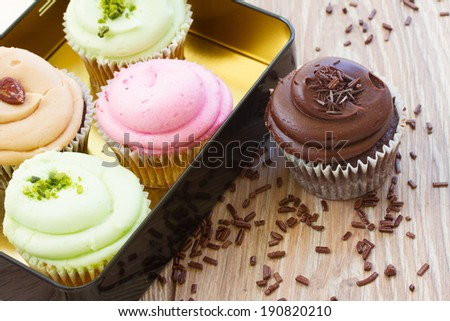 group of fresh cupcakes with chocolate on wooden table - stock photo