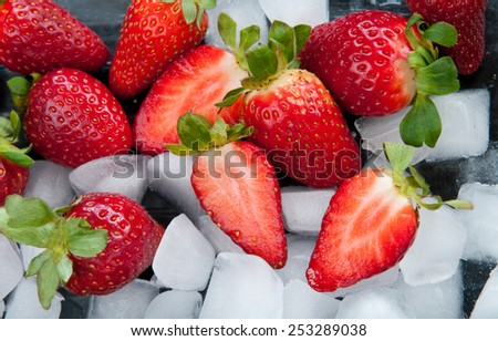 Group of fresh delicious red Strawberries sitting on ice. Strawberries are with green stems and leaves - stock photo