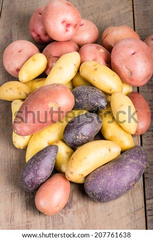 Group of fresh fingerling potatoes on a wooden table - stock photo