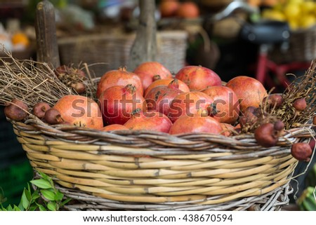 Group of fresh ripe pomegranate fruits in basket on display at local market  - stock photo