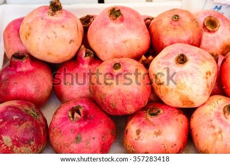 Group of fresh ripe pomegranate fruits in Styrofoam box on display at local market in Geylang, Singapore. Colorful healthy organic pomegranates great for natural food background/publications - stock photo