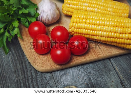 Group of fresh vegetables on a wooden background. tomatoes , corn , garlic close up - stock photo