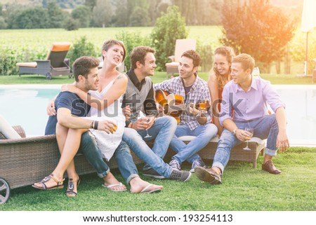 Group of Friend Singing Together next to Swimming Pool