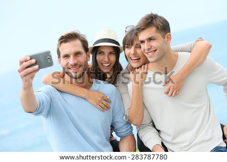 Group of friend taking selfie picture with smartphone - stock photo