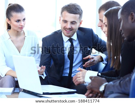 Group of friendly businesspeople gathered in front of laptop  - stock photo