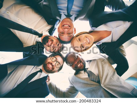Group of friendly businesspeople in suits standing head to head - stock photo