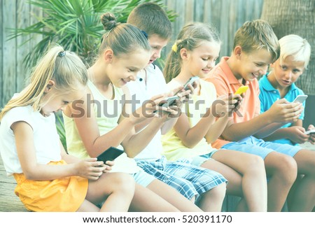 Group of friendly children playing with mobile phones together outdoors
