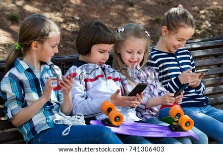 Group of friendly  children posing at urban street with mobile devices