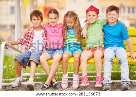 Group of friendly kids sitting on bench outside