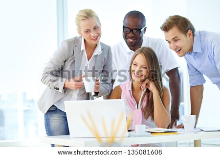 Group of friendly students or businesspeople gathered in front of laptop - stock photo