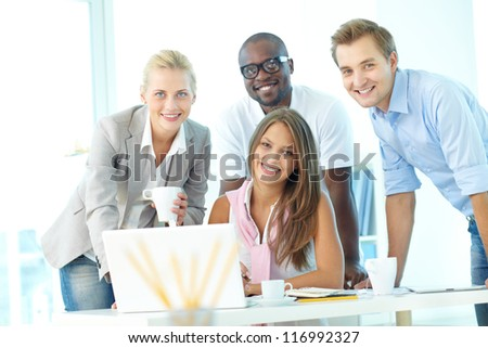 Group of friendly students or businesspeople looking at camera at workplace